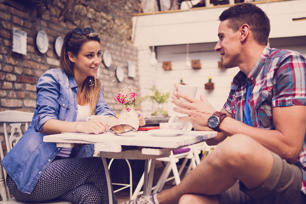 Young happy couple sitting at cafe - How to Attract a Libra Man